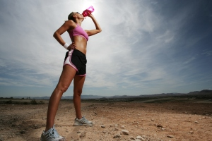 Woman outdoors drinking from a water bottle